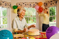 Senior woman and adult daughter preparing birthday party at home, mother placing candles on cake, daughter putting up balloons, smiling