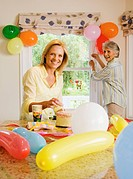 Senior woman and adult daughter preparing birthday party at home, daughter placing candles on cake, mother putting up balloons, smiling, portrait
