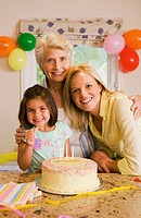 Girl 4-6 sitting with mother and grandmother at table beside birthday cake, making ÔÇÿthumbs upÔÇÖ sign, smiling, portrait