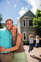 Parents standing in front of detached house, smiling, portrait, excited children 4-6 jumping up and down on driveway, arms up
