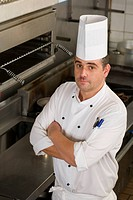 Male chef standing in commercial kitchen, arms folded, portrait, elevated view