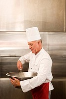 Mature male chef whisking ingredients in large bowl in commercial kitchen, side view