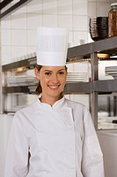 Female chef standing in commercial kitchen, smiling, front view, portrait