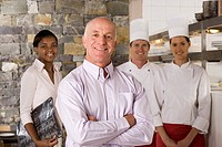 Proud restaurant manager standing with waitress and chefs near commercial kitchen, smiling, portrait