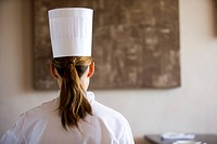 Female chef, with brown hair in ponytail, standing in restaurant, rear view