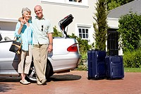 Senior couple standing beside parked convertible car on driveway, smiling, portrait, suitcases on wheels near open boot
