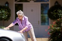 Senior woman polishing silver car parked on driveway in front of house, smiling, side view
