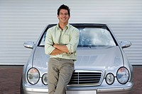 Man leaning on bonnet of parked convertible car on driveway, arms folded, smiling, front view, portrait