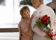 Senior couple standing near water fountain, man holding bouquet of red roses behind back, smiling, portrait