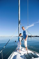 Father and daughter 8-10 standing at bow of sailing boat, smiling, side view, portrait