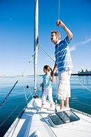 Father and daughter 8-10 standing at bow of sailing boat, holding hands, man leaning on rigging, looking at sea, side view