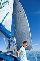Father and daughter 8-10 on deck of sailing boat, man standing beside sails, focus on girl in foreground, smiling, portrait