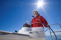 Man in red jacket standing at helm of sailing boat out at sea, smiling, steering, low angle view lens flare