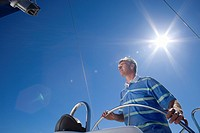 Man in striped blue polo shirt standing at helm of sailing boat out at sea, steering, low angle view lens flare