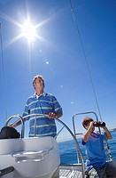 Father and son 8-10 standing at helm of sailing boat out at sea, man steering, boy looking through binoculars lens flare, tilt
