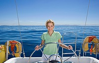 Woman in green polo shirt standing at helm of sailing boat out at sea, steering, smiling, front view, portrait