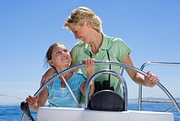 Mother and daughter 8-10 standing at helm of sailing boat out at sea, steering, smiling at one another, front view