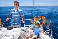 Family relaxing on deck of sailing boat out at sea, father standing at helm, steering, smiling, portrait