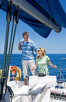 Couple standing at helm of sailing boat out to sea, woman steering, man placing hand on womanÔÇÖs shoulder, smiling