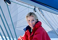 Woman in red jacket sitting on deck of sailing boat below sail, smiling, side view, portrait