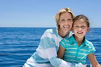 Mother and daughter 8-10 sitting on deck of sailing boat out at sea, smiling, front view, portrait