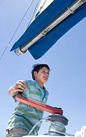 Boy 8-10 winding rope pulley of boat rigging on deck of sailing boat out at sea, smiling, low angle view