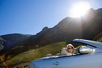 South Africa, Western Cape, senior woman driving silver convertible car along mountain road, smiling, side view, portrait lens flare, tilt