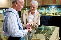 Mature couple in jewelery shop, woman trying on ring, smiling