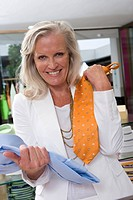 Mature woman in clothing store, holding up shirt and tie, smiling, portrait