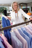 Mature woman in clothing store, holding up shirt, smiling, portrait