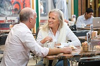 Mature couple sitting in cafe with coffees, smiling at each other