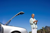 Senior woman experiencing car trouble, standing beside open bonnet, dialling number on mobile phone, smiling