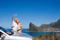 South Africa, Western Cape, senior couple standing beside parked car on clifftop overlooking town and bay, man taking self-portrait with digital camer...