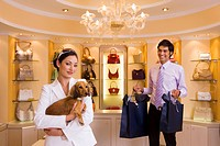 Young woman shopping with dog in glamorous designer handbag boutique, male shop assistant carrying bags, smiling, portrait