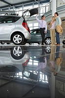 Car salesman showing couple new silver hatchback in car showroom, opening boot, smiling, side view surface level