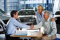 Car salesman and senior couple sitting at desk in large car showroom, two men shaking hands, smiling, side view