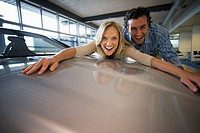 Excited couple embracing bonnet of new silver car in large showroom, smiling, portrait surface level