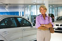 Senior woman standing beside new silver saloon car in large car showroom, smiling, portrait