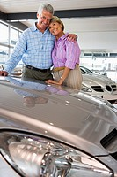 Senior couple standing beside new car in showroom, arms around each other, smiling, portrait