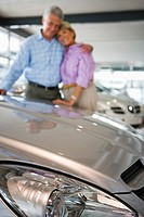 Senior couple standing beside new car in showroom, arms around each other, smiling, portrait, focus on bonnet in foreground