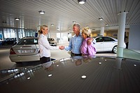Car saleswoman and senior couple standing in large car showroom, saleswoman and man shaking hands, smiling, side view
