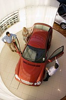 Car salesman showing couple new red hatchback in large car showroom, overhead view