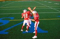 Three American football players, in red football strips, celebrating touchdown on pitch during competitive game, doing high-fives, elevated view
