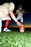 American football player attempting to kick field goal, teammate holding ball vertically against pitch at sunset surface level