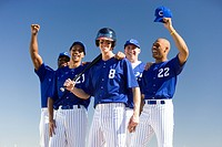 Baseball team, in blue uniforms, celebrating victory post match, arms up, smiling, front view, portrait