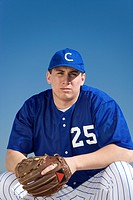 Baseball player wearing blue uniform, protective glove and cap, crouching on pitch, front view, portrait