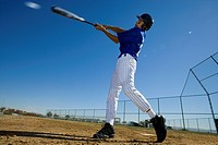 Baseball batter, in blue uniform, hitting ball during competitive game, side view surface level (thumbnail)