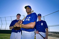 Three baseball players, in blue uniforms and caps, standing on pitch, portrait (thumbnail)