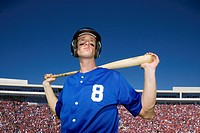 Baseball player, in number ÔÇÿ8ÔÇÖ blue uniform, helmet and face paint, standing on pitch with bat behind head, low angle view, portrait