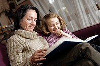 Mother and daughter 6-7 years reading book on sofa